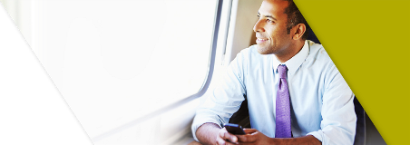 A business man traveling on a train while banking on his phone with the Lead Bank app