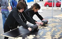 Two students inking a template at the Kansas City Art Institute Road Roller event in Kansas City