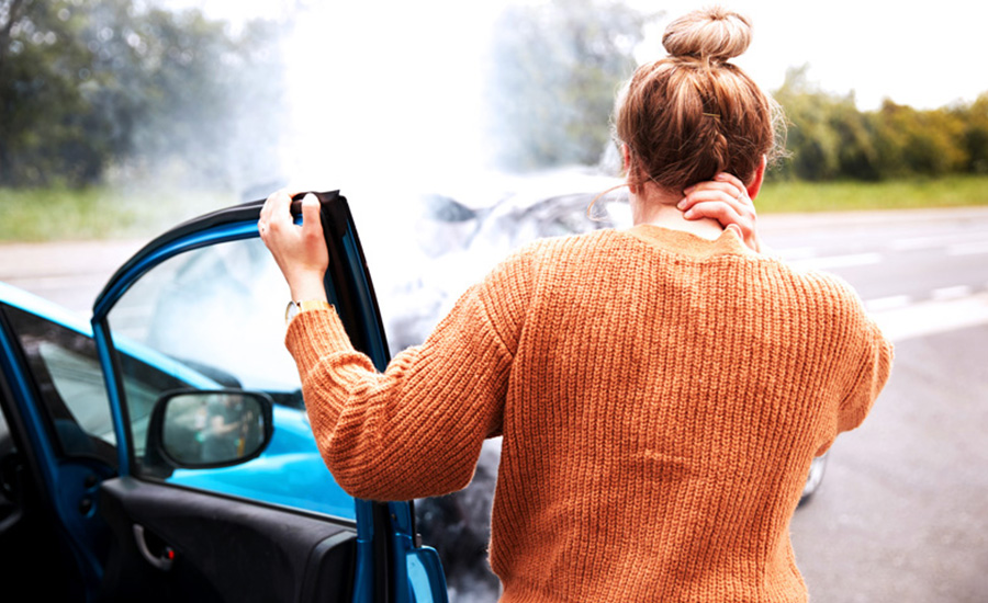 A person holding their neck and investigating damage after an unexpected car accident created an unexpected expense an emergency savings account could help with