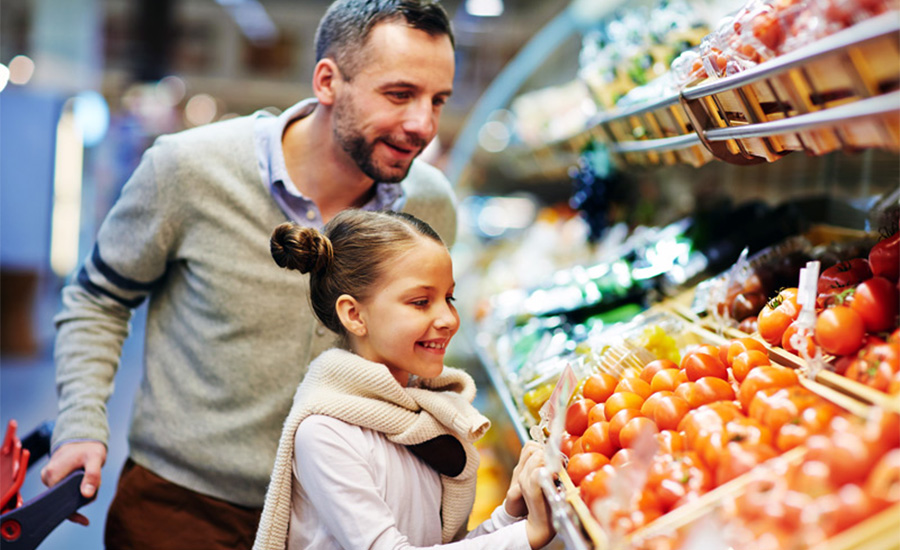 A father and daughter at the grocery store using everyday tips to save money