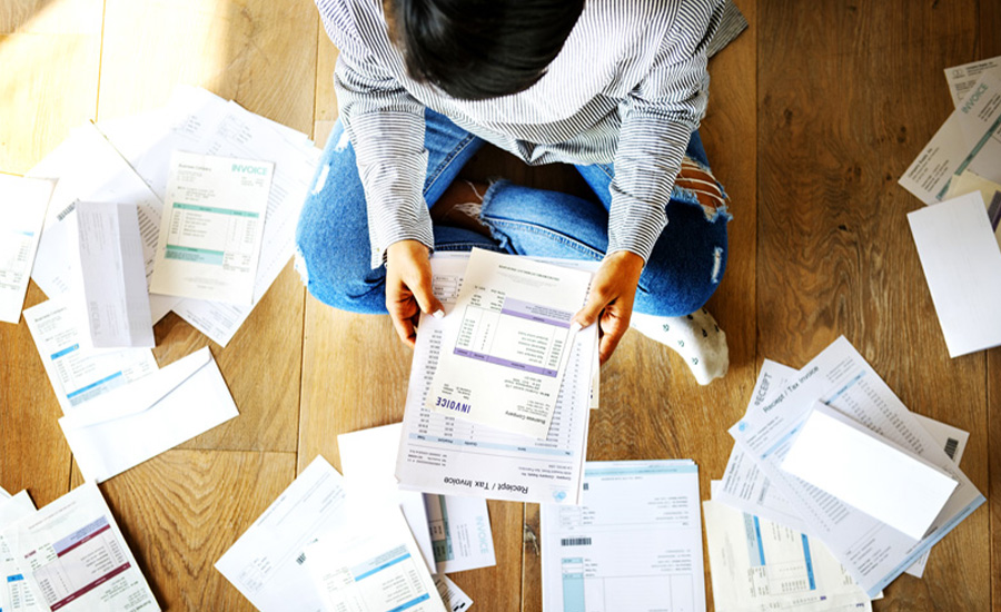 A person reviewing past due credit card bills and budget documents trying to learn how to build credit and pay down debt
