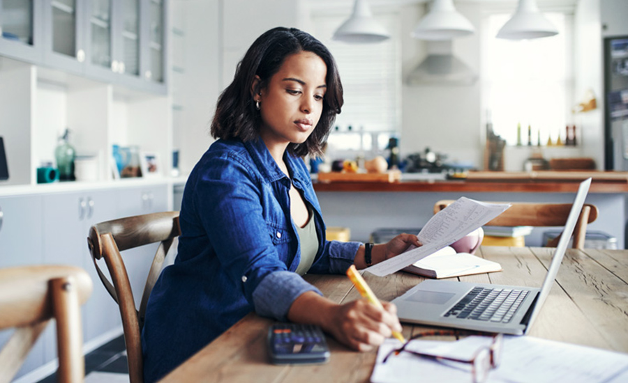 A woman managing her retirement accounts on her computer, trying to determine how much money she will need for retirement