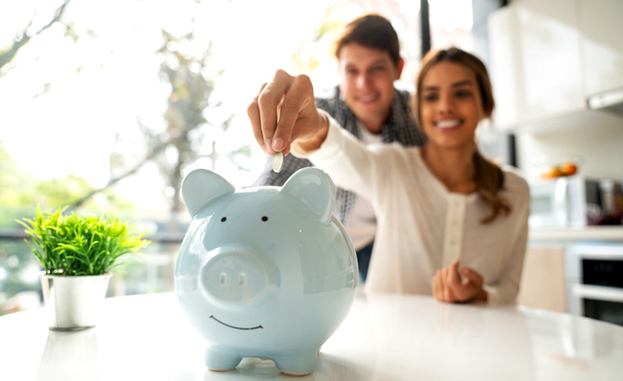 Two people placing money in a cute blue piggy bank after discovering it's never too early to start saving for retirment