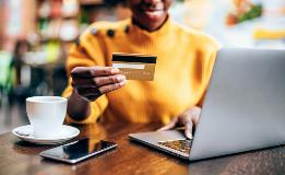 A person shopping using a credit card after following tips to raise your credit score