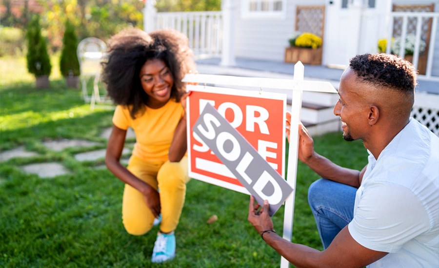 A new homeowner couple placing a sold sign on their first home after discovering why their credit score matters and using the information to buy a house